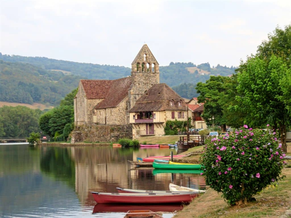 Beaulieu-sur-Dordogne, France, colourful canoes on a river with a chursch at the background