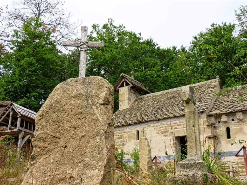 Les Fermes du Moyen Age, France, medieval farms, rural life, Middle ages, open air museum, a cross on a stone and an old house in the background
