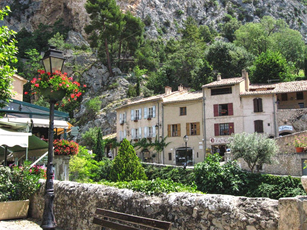 Street in Moustiers-Sainte-Marie, Provence, old stone houses, rocks, flowers