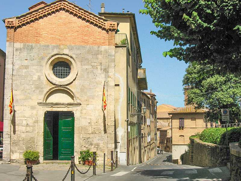an old house with a green door and a round window and a street, street in Volterra Tuscany Italy