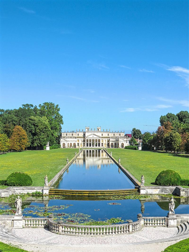 rectangular water pond lined-up with statues in a beautiful green park, villa Pisani along the Brenta canal in Italy with the false stables facade.
