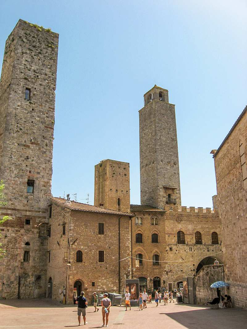 a medieval square with buildings of yellow stone and high towers, Piazza delle Erbe in San Gimignano