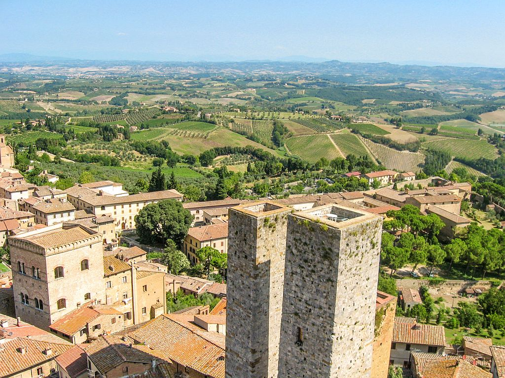 towers of San Gimignano with a bird view to the fields in Tuscany Italy with wine yards and cypresses