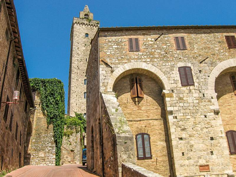 a medieval town in Italy with a tower and houses with wooden shutters, San Gimignano in Tuscany