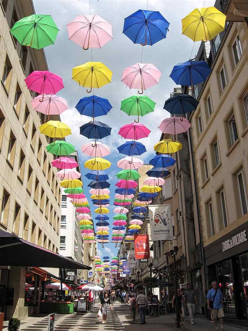 colourful umbrellas hanging in the sky above street level, let the sunshine in project in Luxembourg City