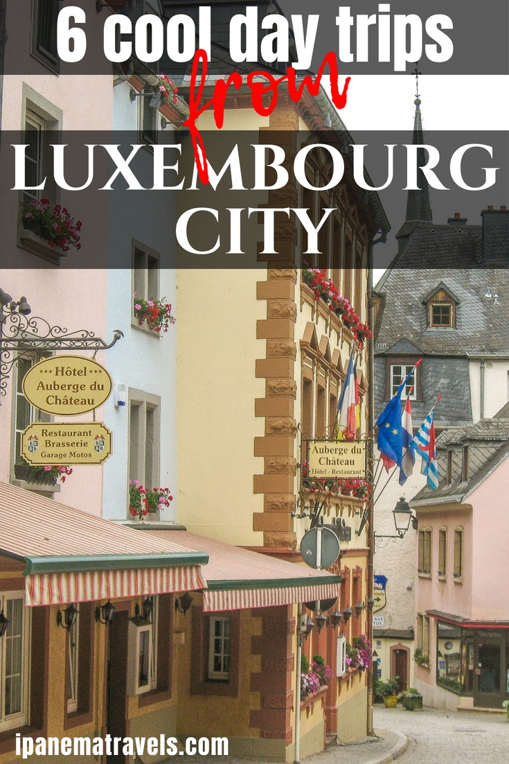 a colourful town with some hanging geraniums on the windows and flags with an overlay text on it: 6 cool day trips from Luxembourg city