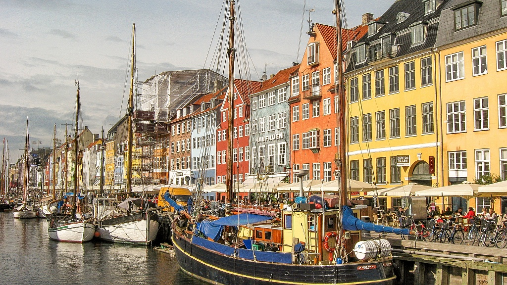 best European city breaks autumn, brightly painted houses and boats in a harbour, Nyhaven in Copenhagen, Denmark