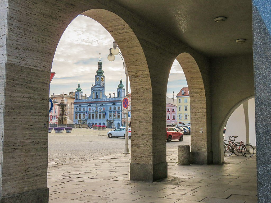 view through an arch to a square with a beautiful blue building with three towers and a fountain, view to square from one of the arcades in Ceske Budejovice, South Bohemia, Czech Republic