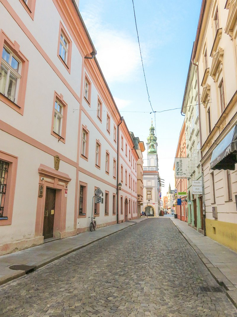 a street leading to a square lined up with buildings with colourful facades in pin, orange, green and peach, a street in Ceske Budejovice in South Bohemia, Czech Republic