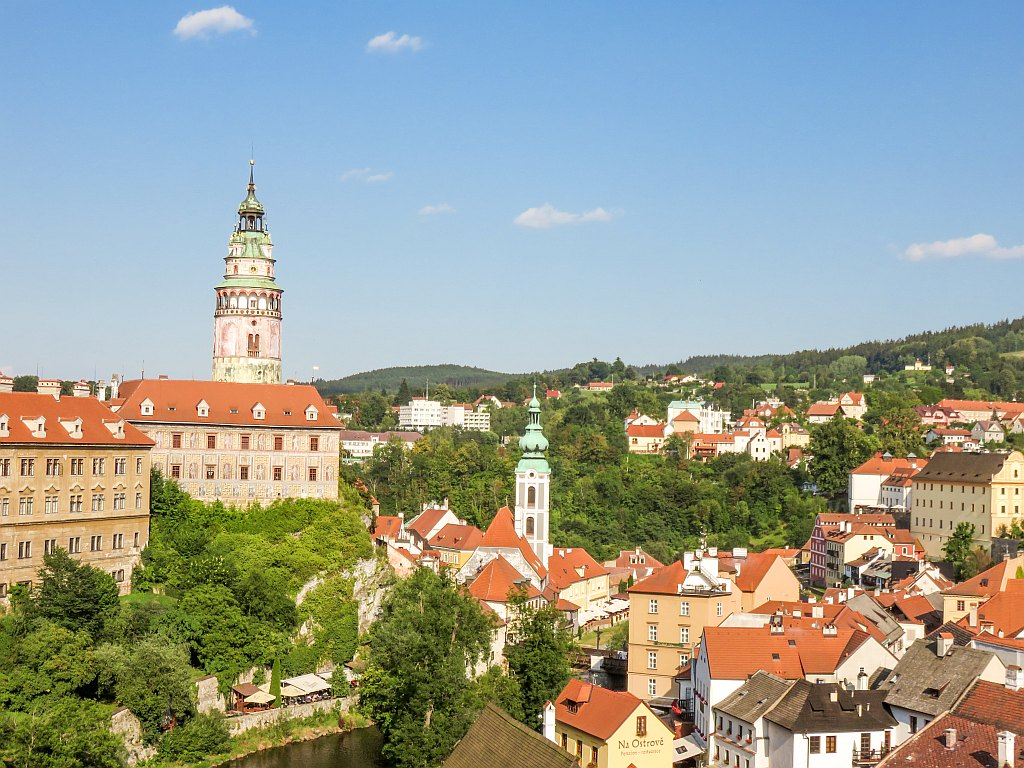 a beautiful castle with a round tower and colourful buildings with red roofs seen from top, a view of the castle in Cesky Krumlov, South Bohemia, Czech Republic