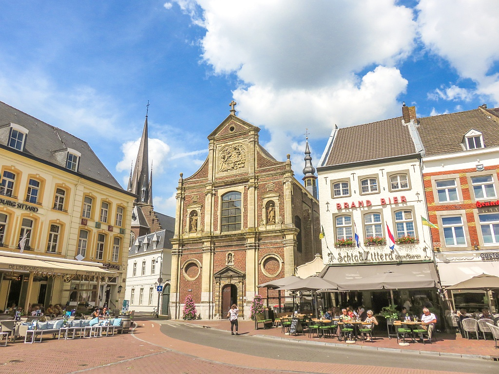 a church on a city square with blue sky; the best day trips from Maastricht in Limburg the Netherlands