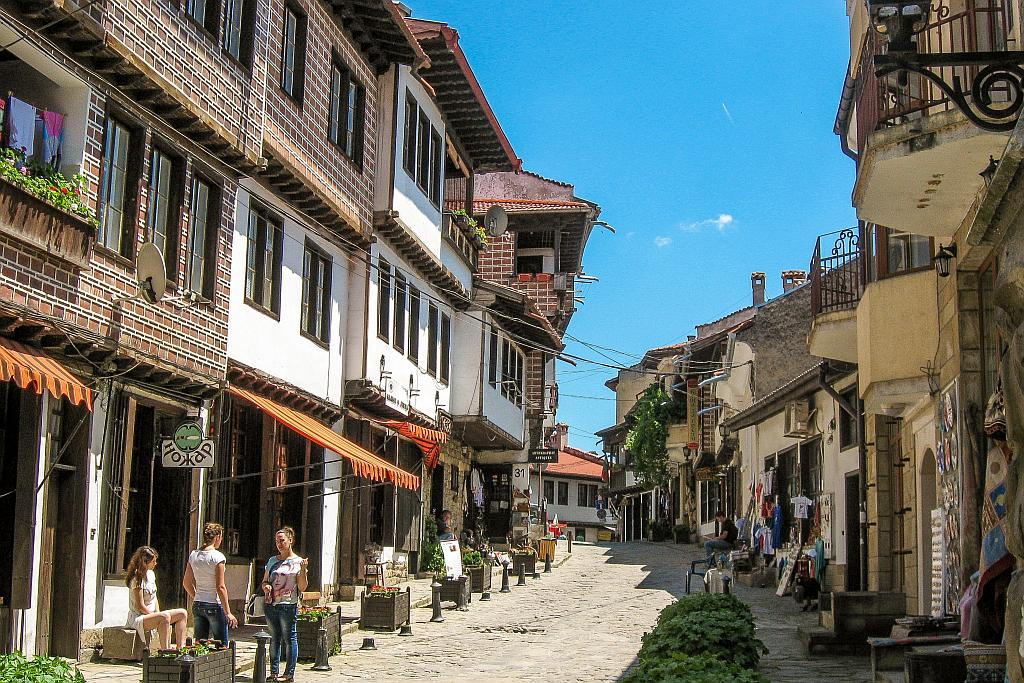 a cobblestone street with houses on both sides and little shops on the ground floor, Samovodska charshia Veliko Tarnovo