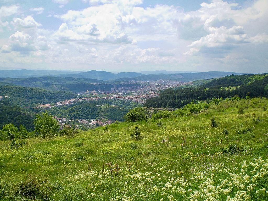 lush green hills dotted with spring flowers and a city at the distance with some hilly mountains, Veliko Tarnovo seen from Arbanassi
