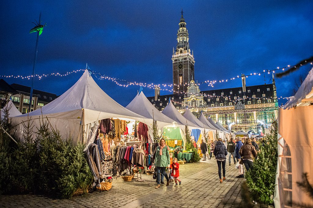 white tents on a market with scattered Christmas trees around for sale and a church belfry at the background, the Christmas Market in Leuven
