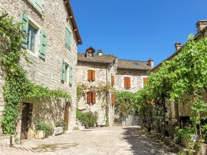 stone houses on a small square with vines hanging above the sidewalk, summer destination in europe