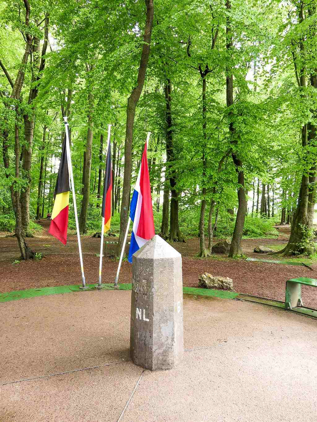 a border stone with the flags of the Germany, Netherlands and Belgium behind, Three-country point at Vaals