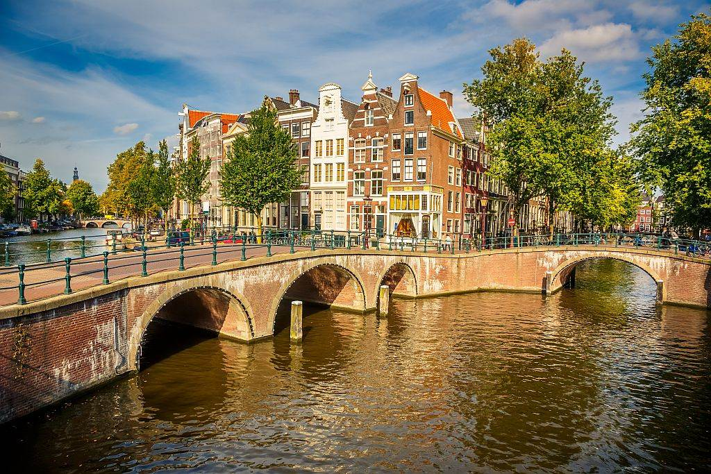 canal with rounded bridges and houses with bell gables - Amsterdam