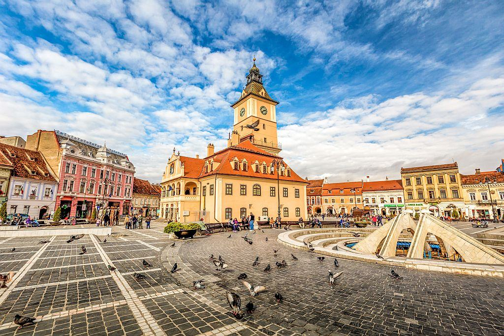 a city square with pigeons and a beautiful yellowish building with a clock tower, Brasov, Romania
