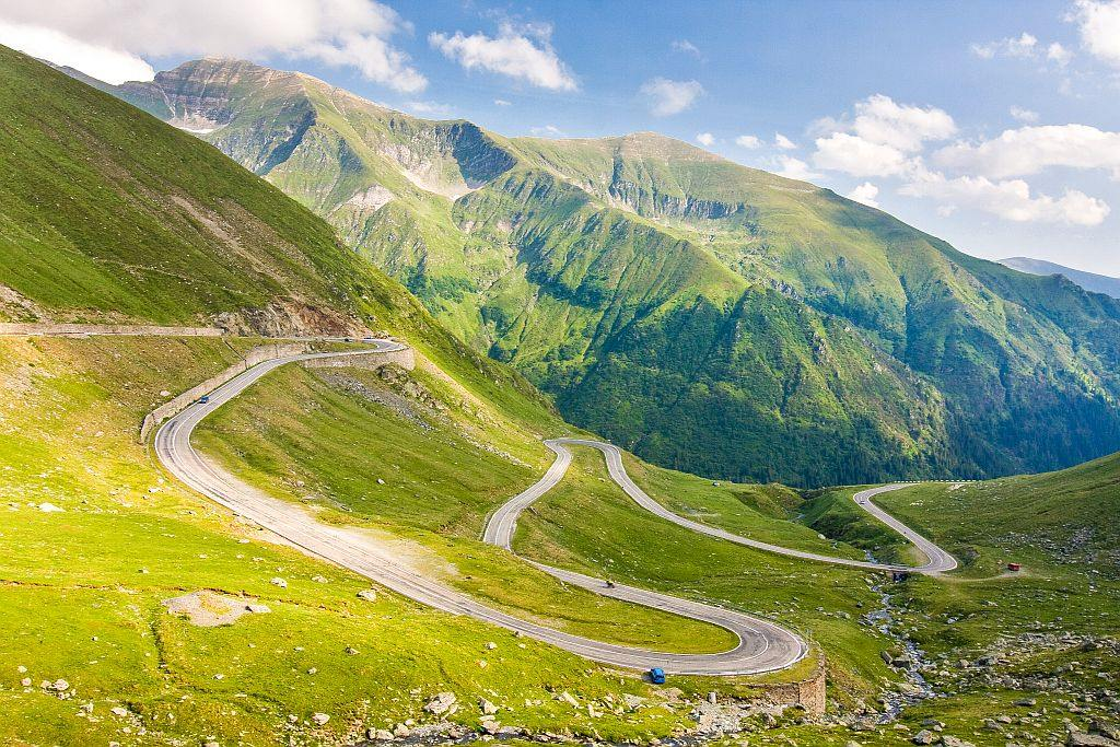 a winding road with hairpin bends in a green mountain, the Transfagarasan mountain road in Romania