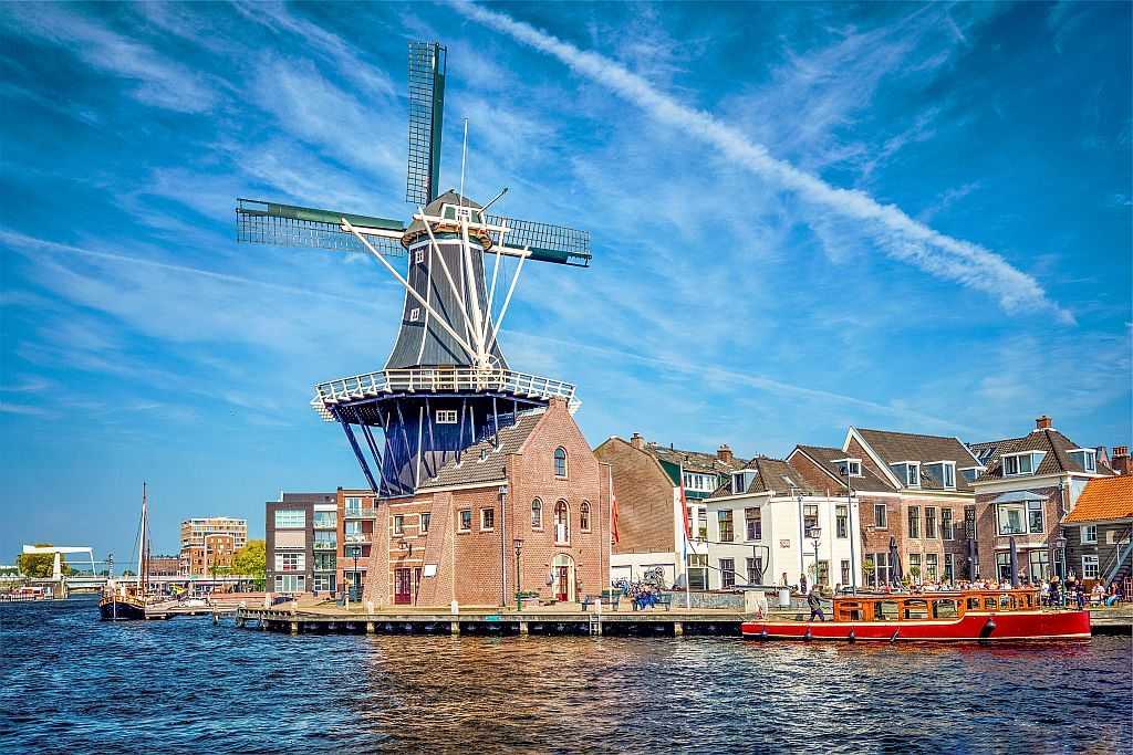 a black wooden windmill with some old houses on a wharf and a red barge in the water, Haarlem