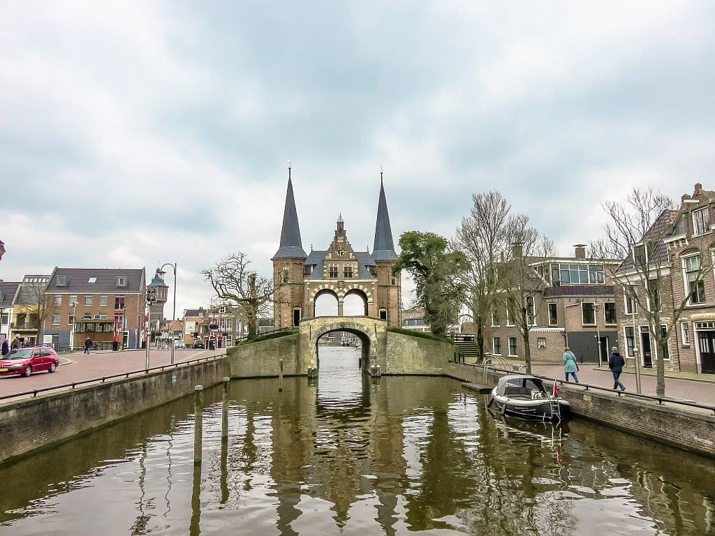 a bridge over a canal with a building with two spires, Sneek
