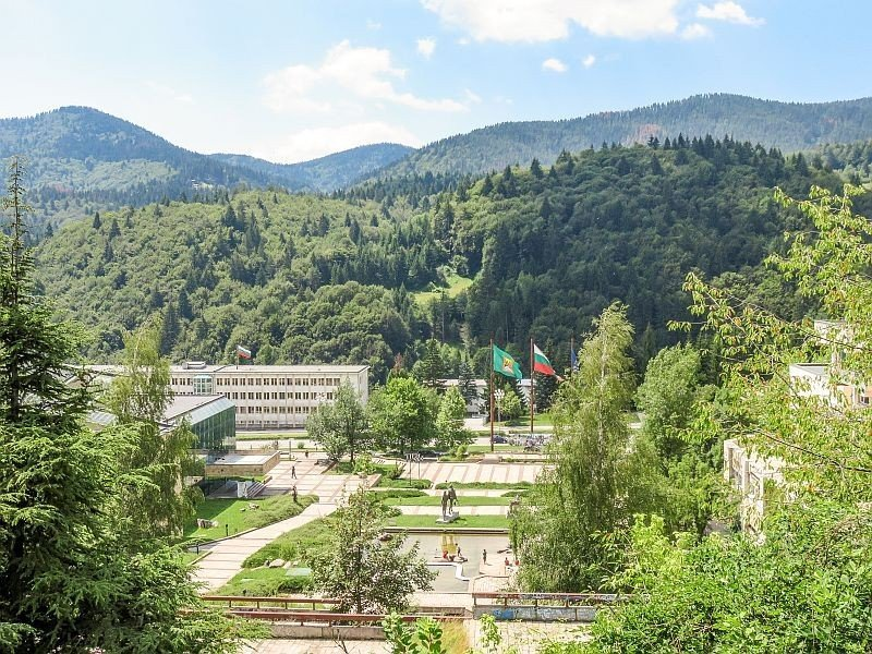 a city in the mountains with white building and two flags in the middle of park, Smolyan