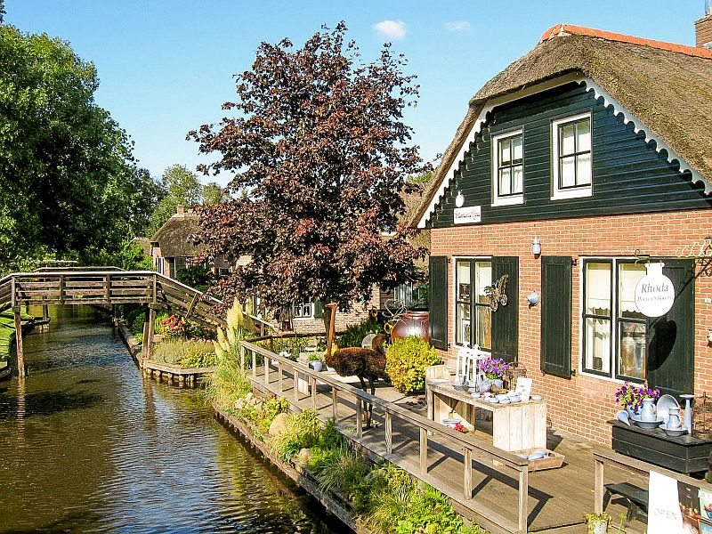 a beautiful house on a canal and some wooden bridges at the background, Giethoorn in the Netherlands