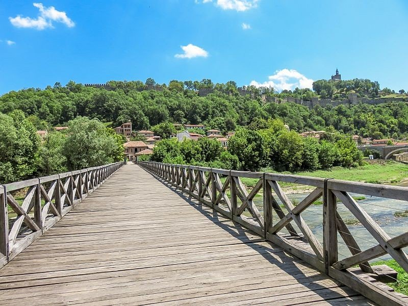 a wooden bridge above the river leading to a green hill with a fortress on it, the Bishop's Bridge in Veliko Tarnovo, Bulgaria