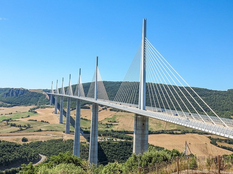 a huge and tall bridge above a river with spires and metal ropes coming from the spires to the road level, the Millau Viaduct