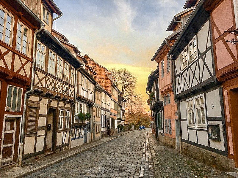 a cobblestone street lined up with half-timbered houses and a sunset at the end of the street, Quedlinburg in Germany