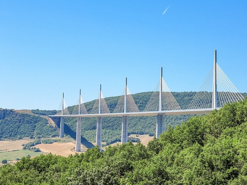 a cable-stayed bridge with some green hills behind, the Viaduct of Millau