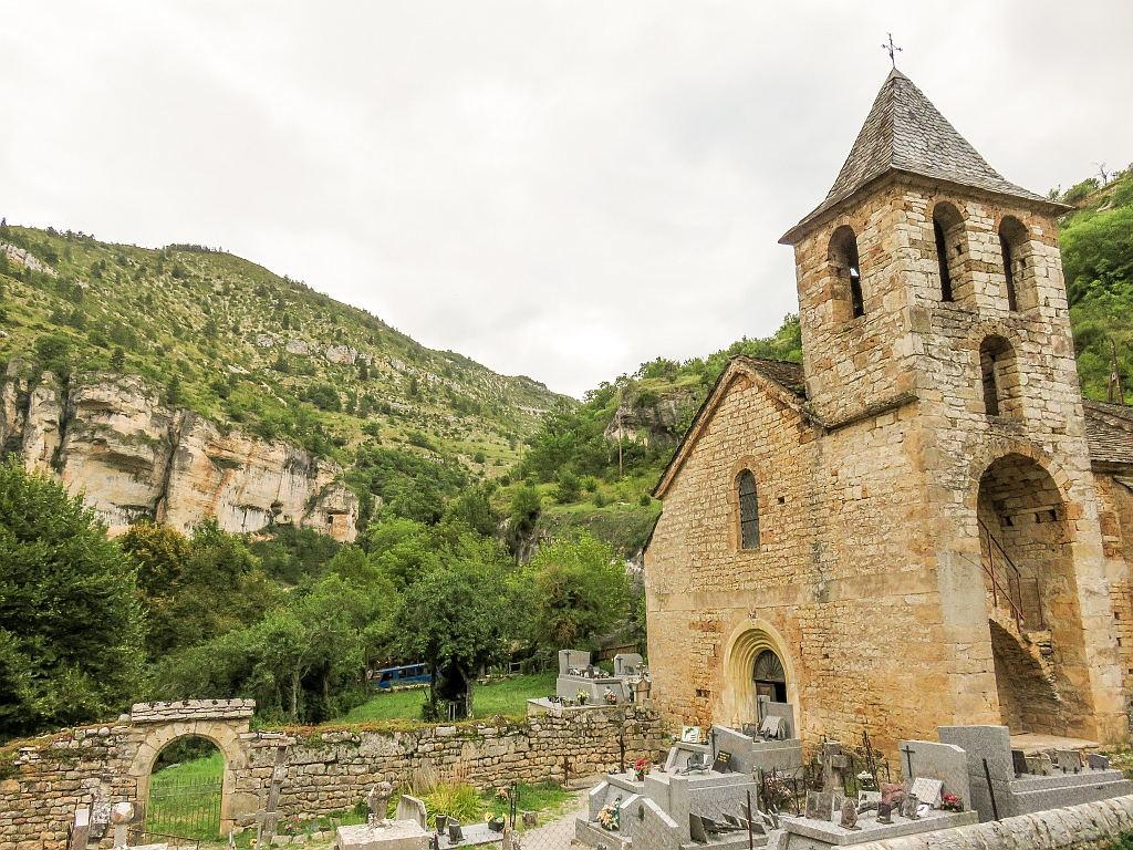 a small medieval church with a graveyard and green hills with cliffs behind, the church in Saint-Chely-du-Tarn