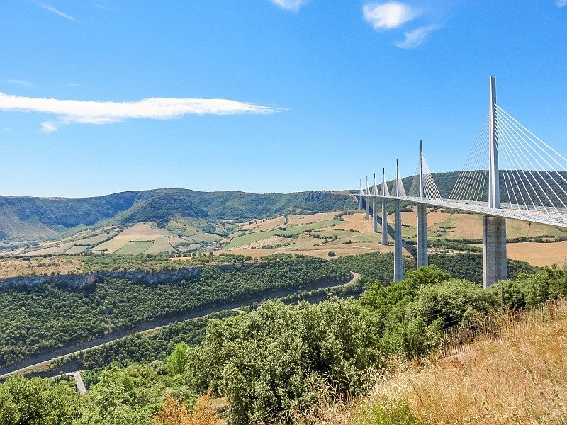 a bridge with high pillars and a beautiful green and yellowish landscape with rolling hills and blue sky above with white clouds, a view from the Millau Viaduct