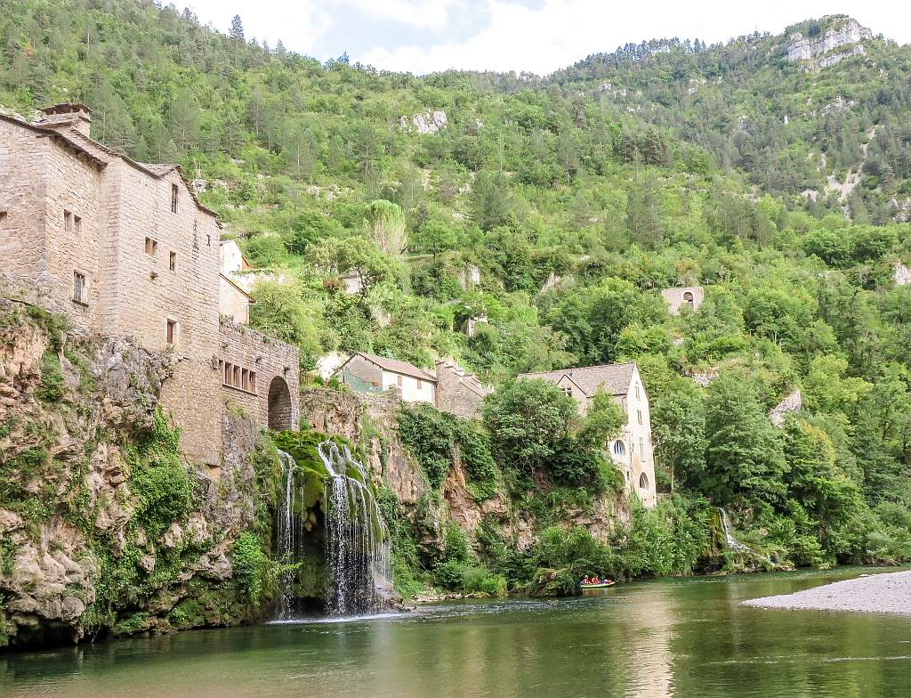 two small waterfalls with houses on the rock, a green river and green hills, a boat with people in the vicinity, Saint-Chely-du-Tarn in France