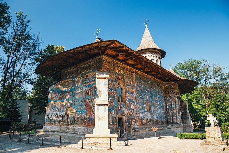 a church with a beautifully painted exterior predominantly i blue, the Voronet Monastery in Romania