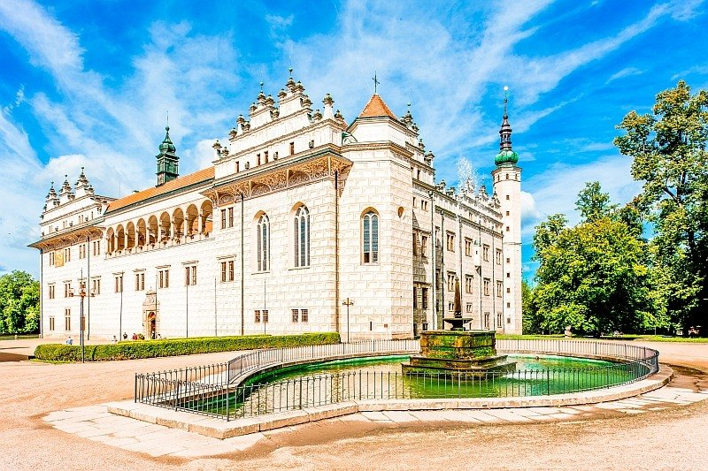 a white castle with ornated facade and a small pond at the front with a fountain in the middle, Litomysl Palace in Czech Republic