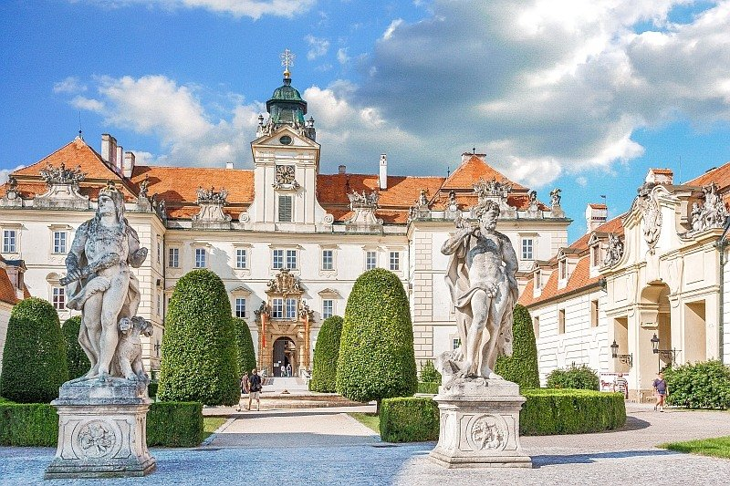 a white building with a red-tiles roof, with ornated facade and two statues in front with green low hedges and box tree columns, the Valtice Castle Czech Republic