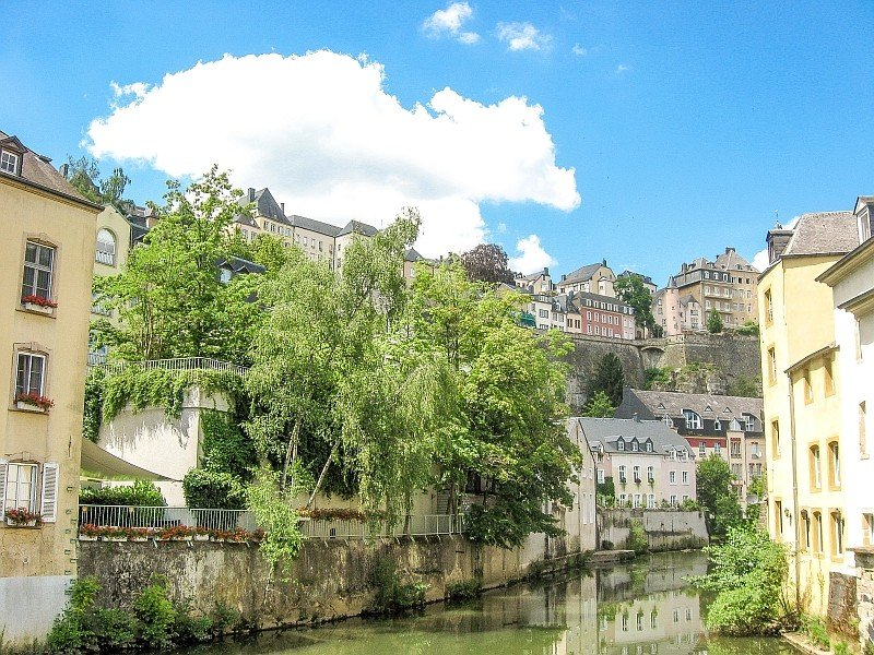 a greenish river with yellowish buildings on both banks and some green trees and the buildings reflecting in the water, Alzette River in Luxembourg City