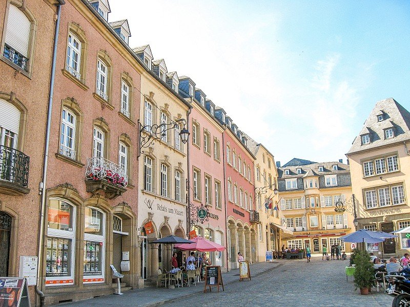 colorful houses on a square with blue sky and people sitting in cafes on the sidewalk and the square, Echternach in Luxembourg