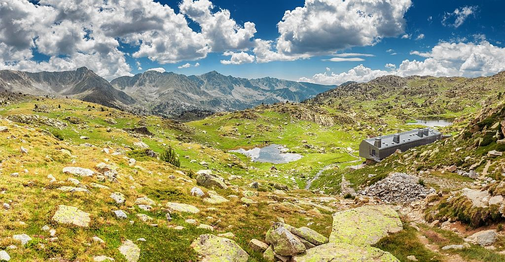 a vew to a plateau and steep mountain tops with a small lake in the middles and white clouds on a blue sky, UNESCO Madriu-Perafita-Claror Valley in Andorra