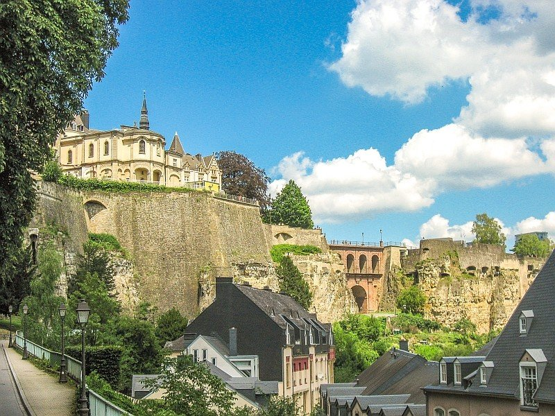 a high wall with a castle on top and a reddisch arched bridge in the middle and some houses with grey roofs in the foreground, Luxembourg Old Town