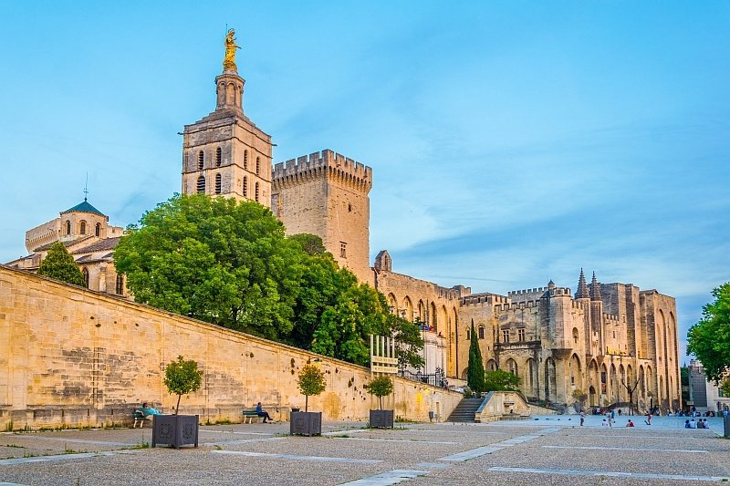 a large medieval building like a castle with towers and a church adjacent with the sunset reflecting on the sand stone walls against blue sky, the Cathedral and the Palace of the Popes in Avignon