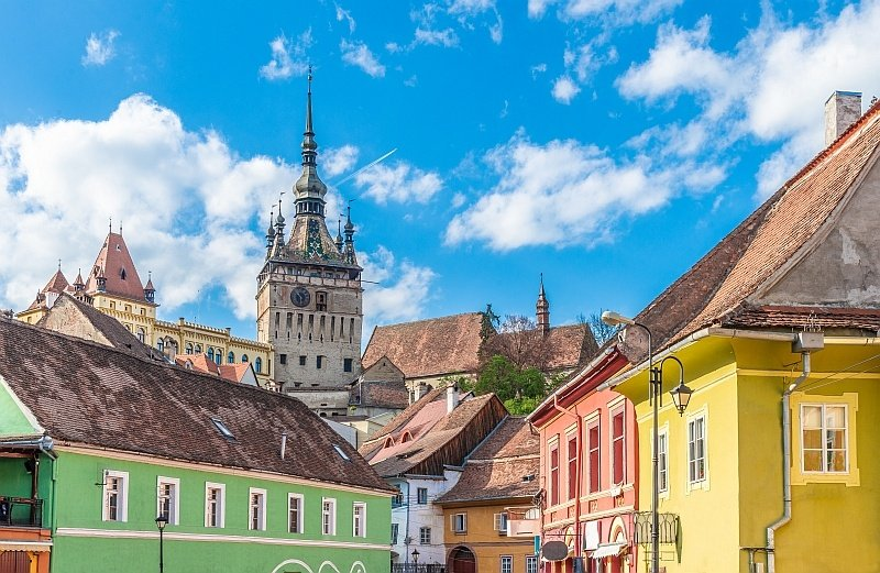 candy-colored houses and a clock-tower against blue sky with some fluffy white clouds, Sighisoara in Romania