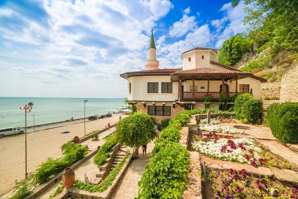 a white building with a minaret type of a tower with flower garden in front and the seashore to the right, Balchik palace and Gardens in Bulgaria