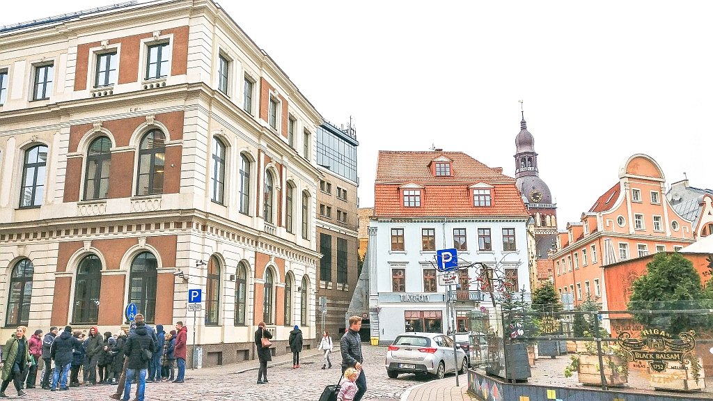 a square in a city with lovely buildings and a church tower at the background, Riga