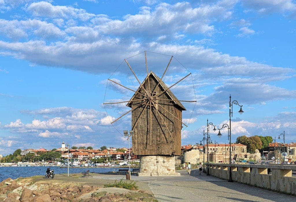 a wooden windmill on a small piece of land leading to a promontory with a town, Nesebar in Bulgaria