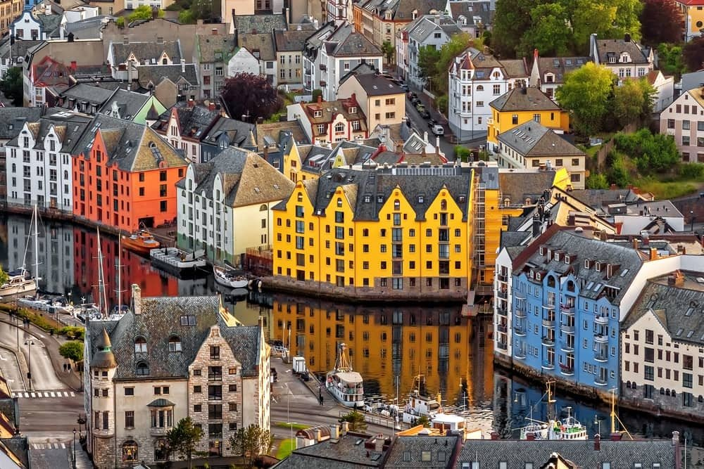 a bird's-eye view of colorful buildings alongside a water canal, Alesund, Norway