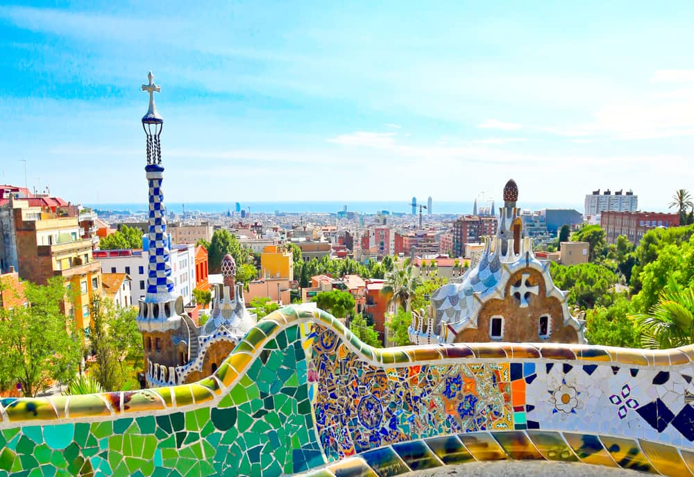 a low wall covered with broken pieces of colorful tiles and fantastic towers and a city view at the background, Park Guell in Barcelona